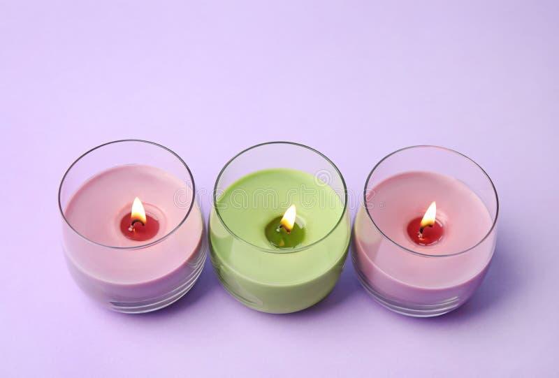 Горя свечи воска в стеклянных держателях на пурпуре стоковая фотография rf