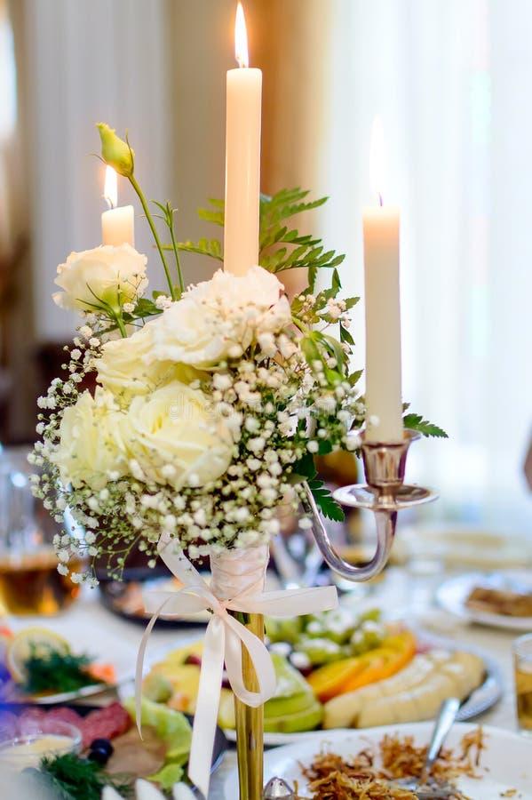 Горя свечи в подсвечнике, украшенном со стойкой цветков на таблице в ресторане стоковое фото rf
