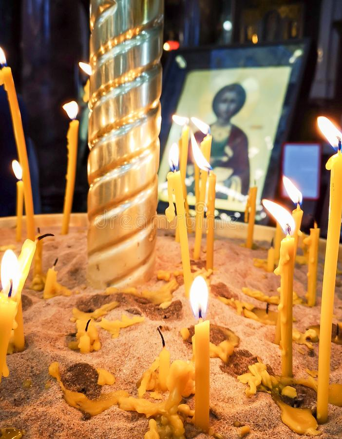 Горя свечи в православной церков церков, которую верующие освещают и устанавливают перед значками Святых с молитвами стоковое изображение rf