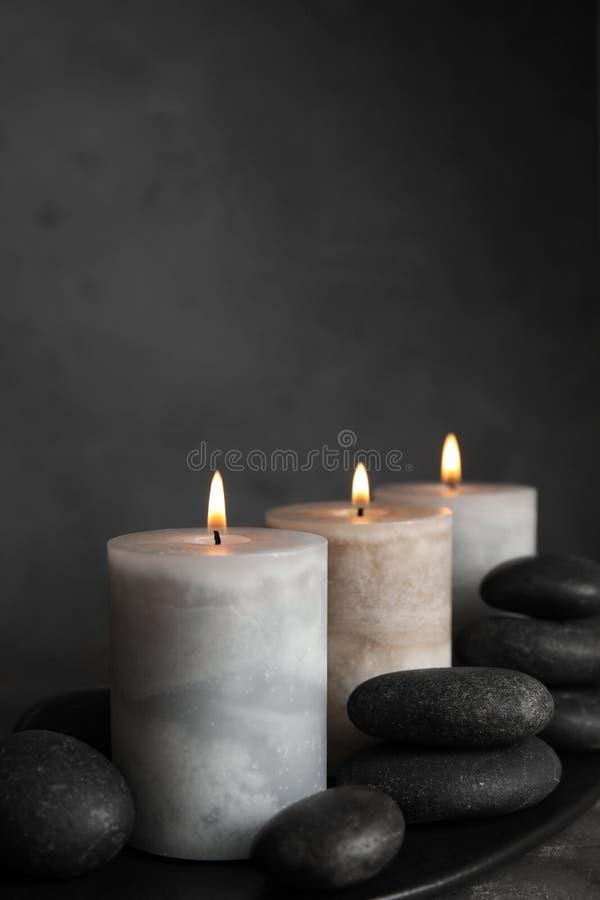 Горя свечи и камни спа на черной плите стоковые изображения rf