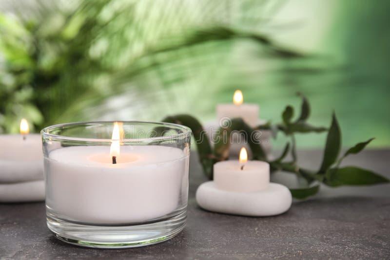 Горя свечи, камни спа и бамбуковый росток на серой таблице против запачканной зеленой предпосылки стоковое фото rf
