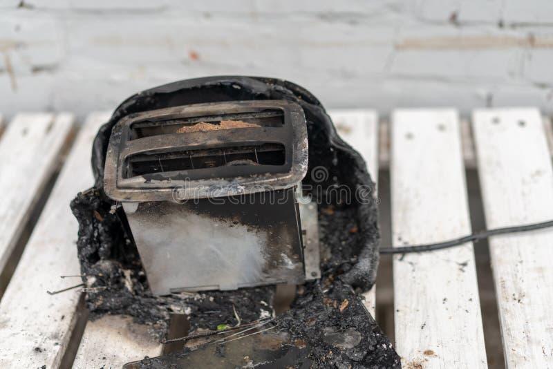 Горя тостер Тостер с 2 кусками тоста уловил горящее над белой предпосылкой стоковые изображения