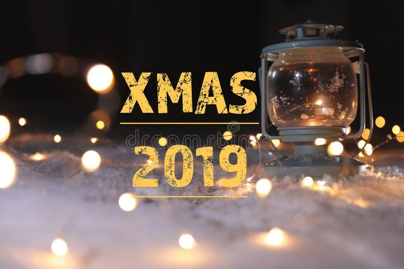Горя фонарик со светами рождества на XMAS 2019 снега и сообщения против темной предпосылки стоковые фото
