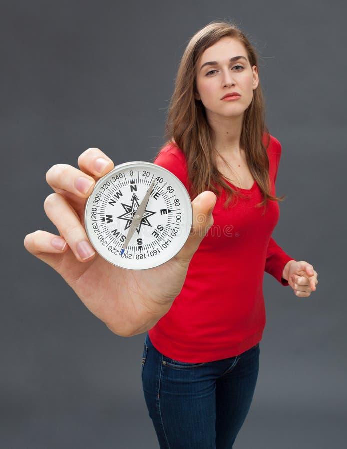 Гордая молодая женщина при bossy жест рукой показывая компас стоковое фото rf