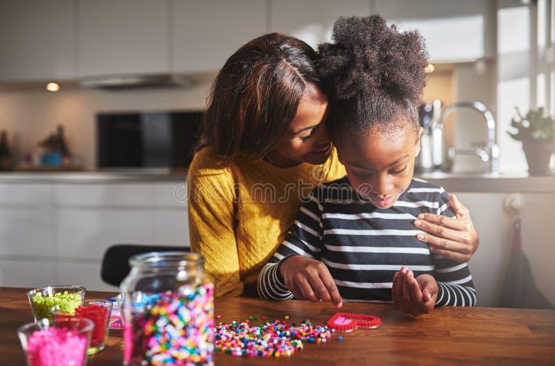 Гордый родительский обнимая ребенок делая ремесла стоковое изображение