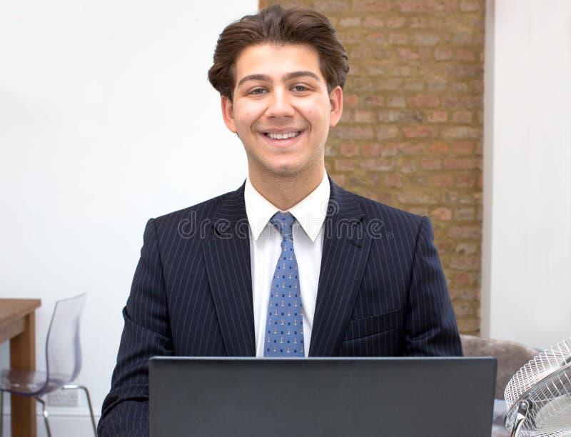 Гордый усмехаясь молодой бизнесмен на его столе стоковые фотографии rf