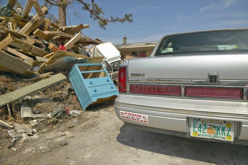 Гордый для того чтобы быть американскими наклейкой на бампере и твердыми частицами перед домом тяжело ударил ураганом Иваном в Pe стоковая фотография rf