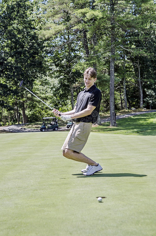 Госпож удар, загоняющий мяч в лунку гольфа стоковая фотография rf