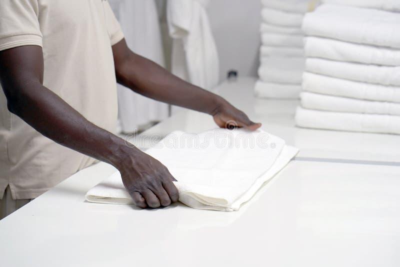 Гостиница прачечной Человек кладет вне белое полотенце стоковые фото