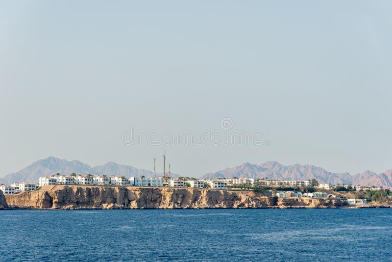 Гостиницы и дома в стойке расстояния над скалой над голубым морем стоковые изображения rf