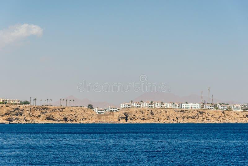Гостиницы и дома в стойке расстояния над скалой над голубым морем стоковое фото