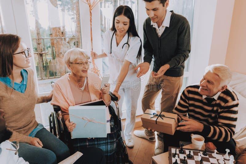 Гости дают мобильный телефон женщине Дом престарелых стоковое фото rf