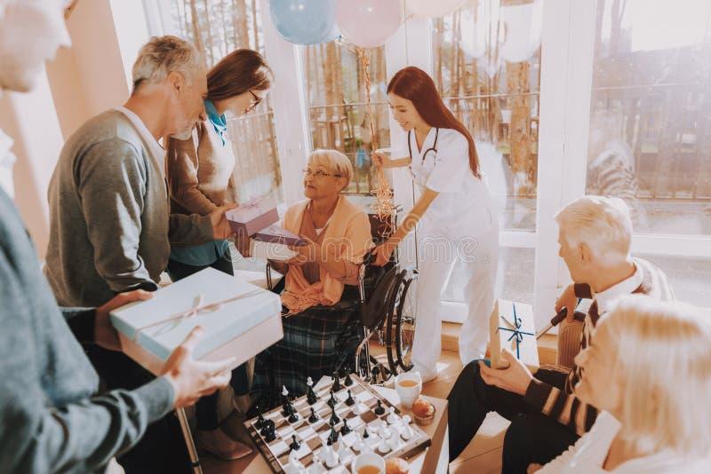 Гости дают подарки пожилой женщине именниный пирог воздушных шаров афроамериканца красивейший празднует время партии дома удержив стоковое изображение