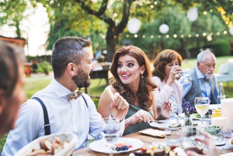 Гости есть на приеме по случаю бракосочетания снаружи в задворк стоковое фото