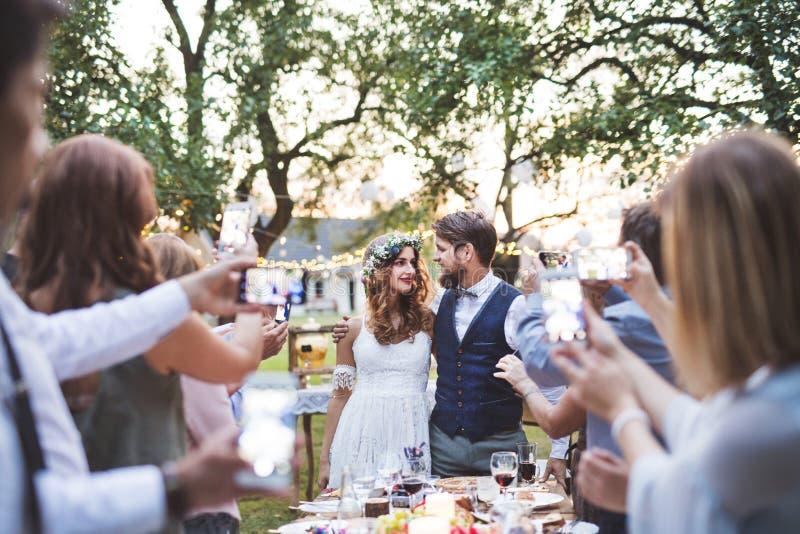 Гости при smartphones принимая фото жениха и невеста на прием по случаю бракосочетания снаружи стоковое фото rf