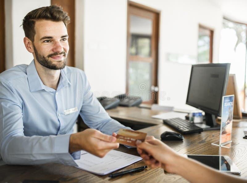 Гости проверяя внутри с оплатой кредитной карточки к гостинице стоковые изображения