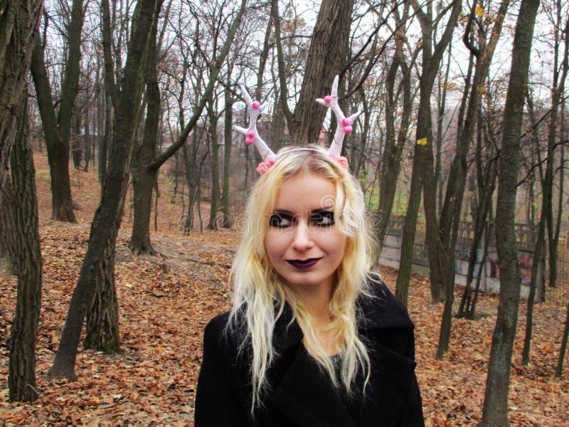 Готическая девушка в новогодней копытке с оленьими рогами в лесу стоковые изображения rf