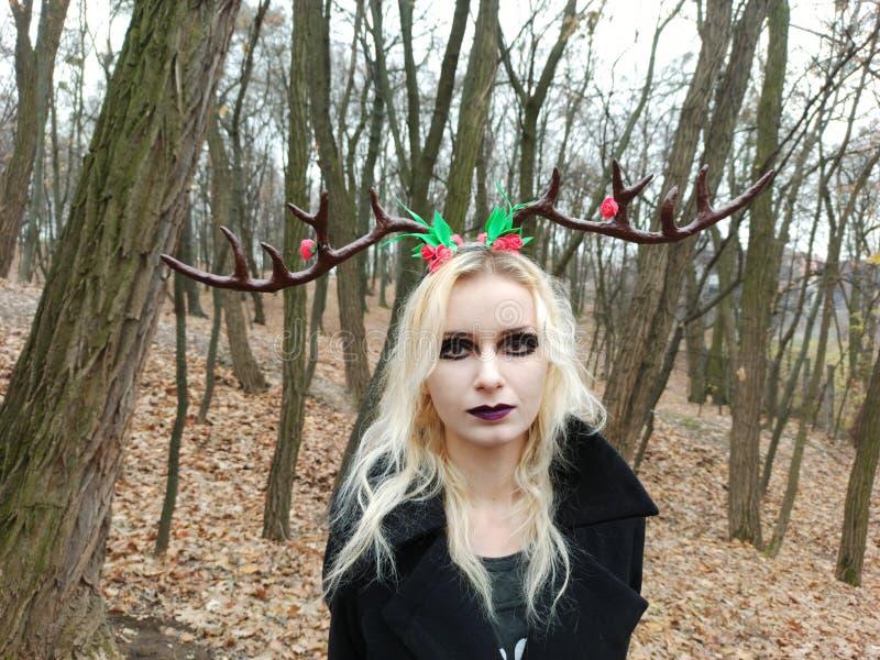 Готическая девушка в новогодней копытке с оленьими рогами в лесу стоковые изображения