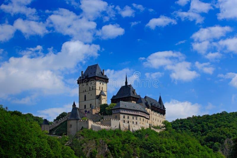 Готический королевский замок Karlstejn в зеленом лесе во время лета с голубым небом и белыми облаками, центральной Богемией, чехи стоковые фото
