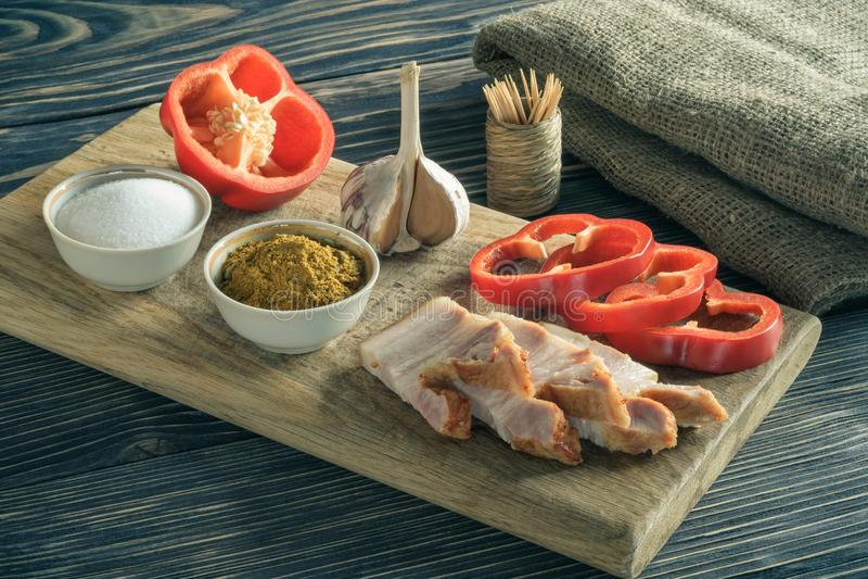 готовая закуска отрезанный?? грудинка свинины с перцем, чесноком и специями на разделочной доске на старой серой деревянной предп стоковое фото