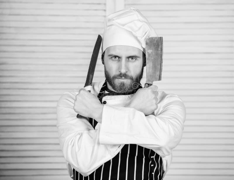 Готово к работе уверенный человек в фартуке и ножом для шляпы бородатый человек любит есть еду готовить в ресторане, униформу стоковые фотографии rf