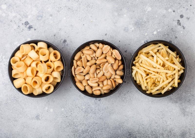 Готовые посоленные кольца картошки с ручками соли и уксуса и зажаренными в духовке арахисами как классическая закуска в черных ша стоковое фото