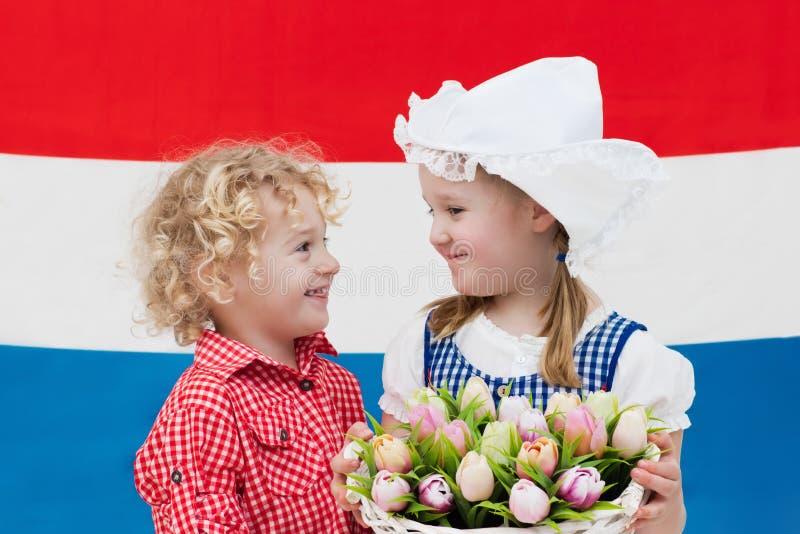 Голландские дети с цветками тюльпана и нидерландским флагом стоковое изображение rf