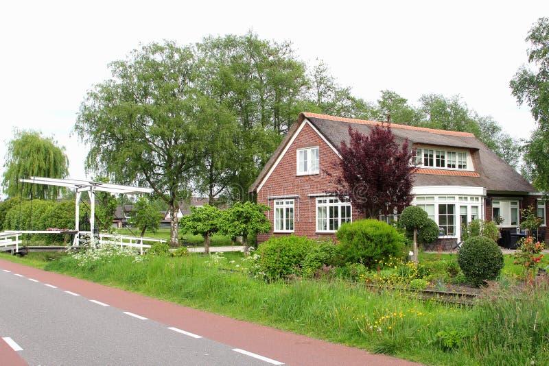Голландский загородный дом с садом, каналом и перекидным мостом, Нидерландами стоковые изображения