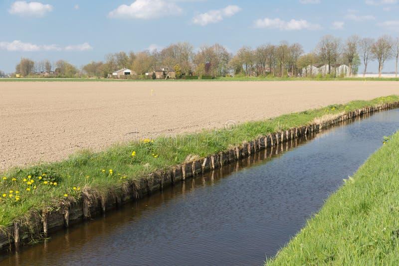Голландский сельский ландшафт с рвом и обрабатываемой землей стоковая фотография