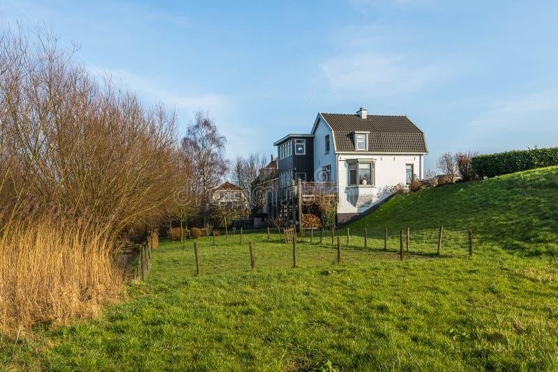 Голландцы благоустраивают с домами в dike стоковые изображения
