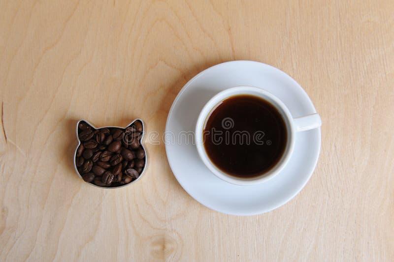 Голова кота кофейных зерен и чашки кофе на поддоннике На светлой древообразной предпосылке, взгляд сверху стоковое изображение