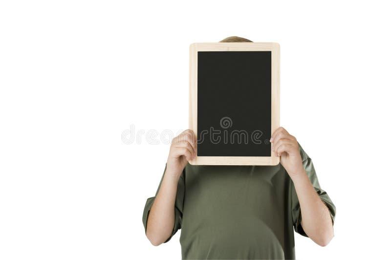 Голова мальчика за черной доской стоковое фото rf