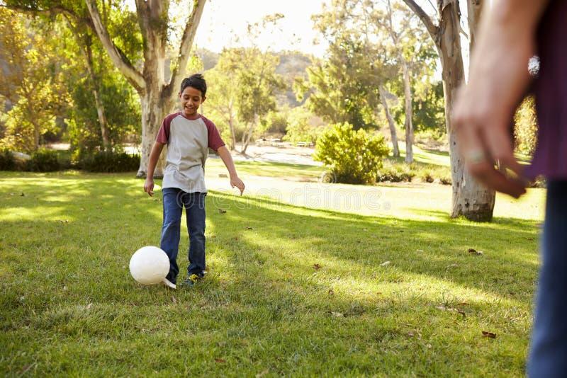 Годовалый мальчик 7 играя футбол в парке с папой стоковые изображения rf