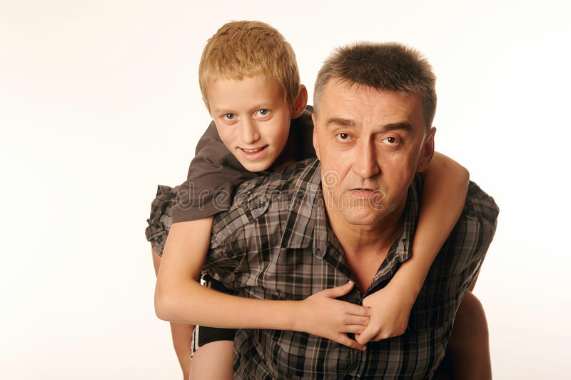 Годовалый сын 10 жизнерадостно обнял его отца сидя на его назад стоковая фотография