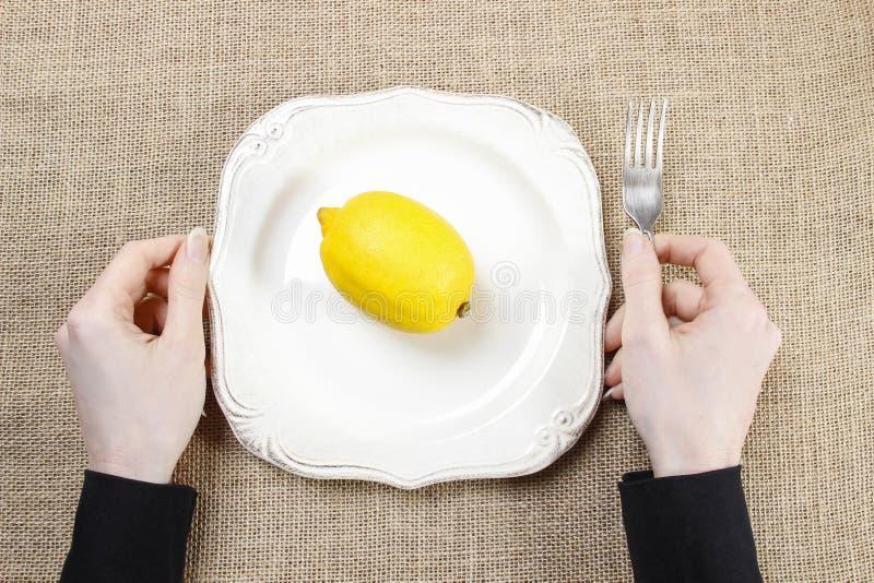 Голодная женщина есть лимон Символ приспосабливаться к новой культуре стоковая фотография rf