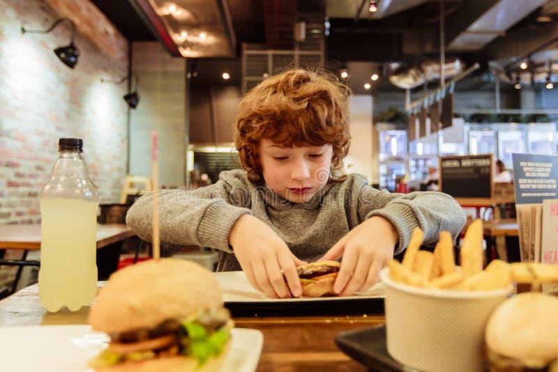 Голодный мальчик ест бургер в ресторане стоковая фотография