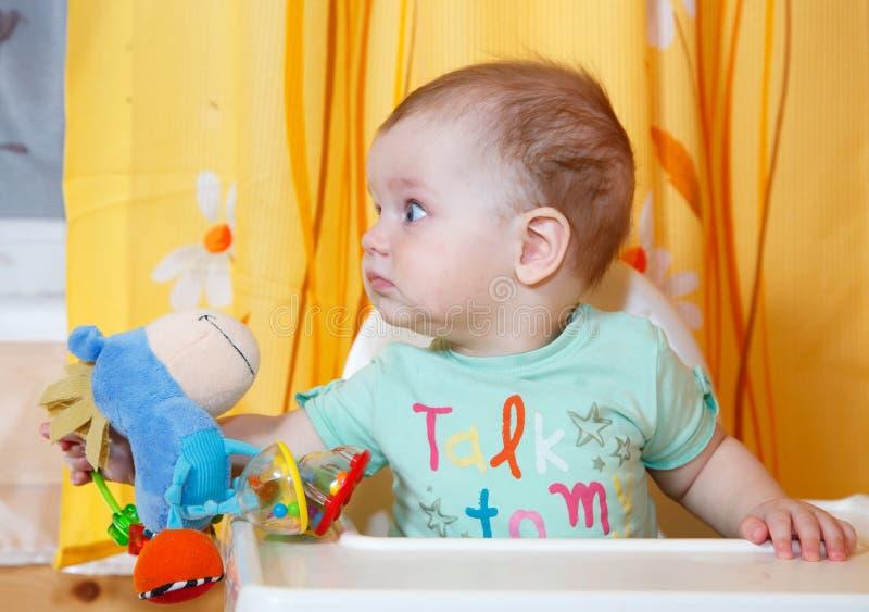 Голодный младенец с игрушкой в его еде руки ждать стоковое фото