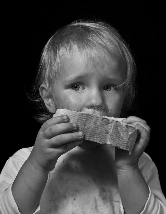 Голодный ребенок есть хлеб стоковые изображения rf