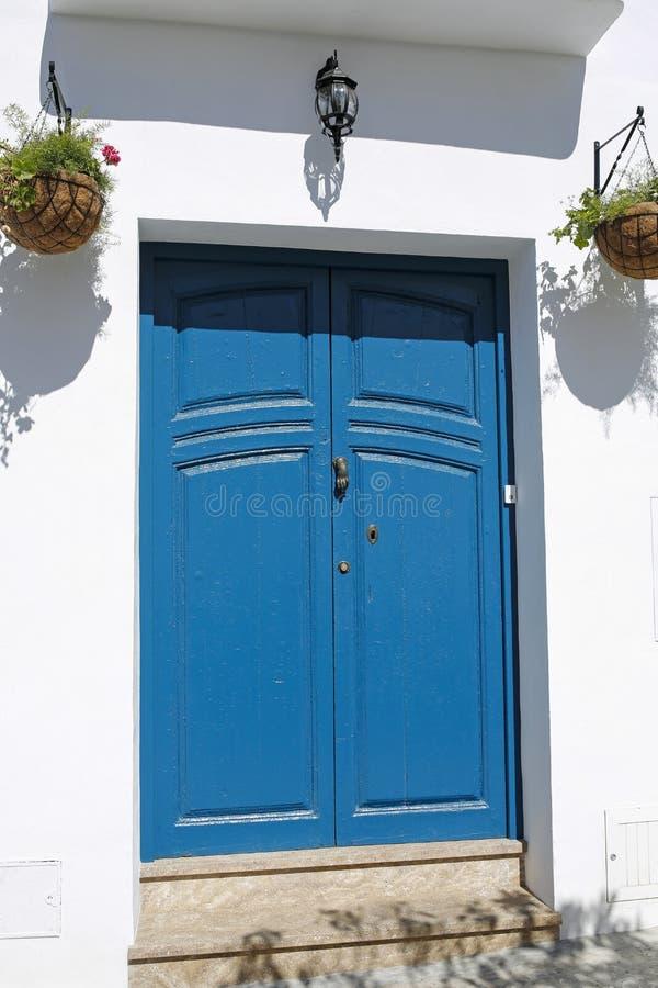 Голубая деревянная дверь украшенная с цветками стоковая фотография rf