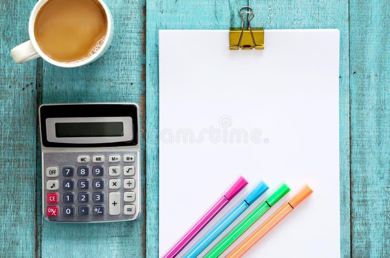 Голубая деревянная таблица с бумажным ream, ручка стола цвета, калькулятор стоковые фото