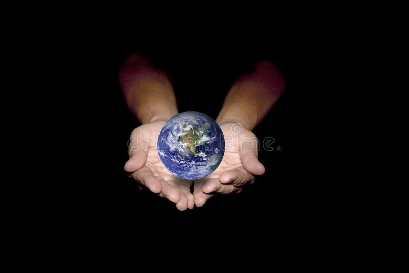 Голубая земля в человеческих руках изолированных на черной предпосылке стоковые фото
