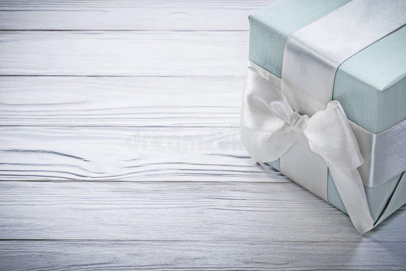 Голубая подарочная коробка с белым узлом на conce торжеств деревянной доски стоковая фотография