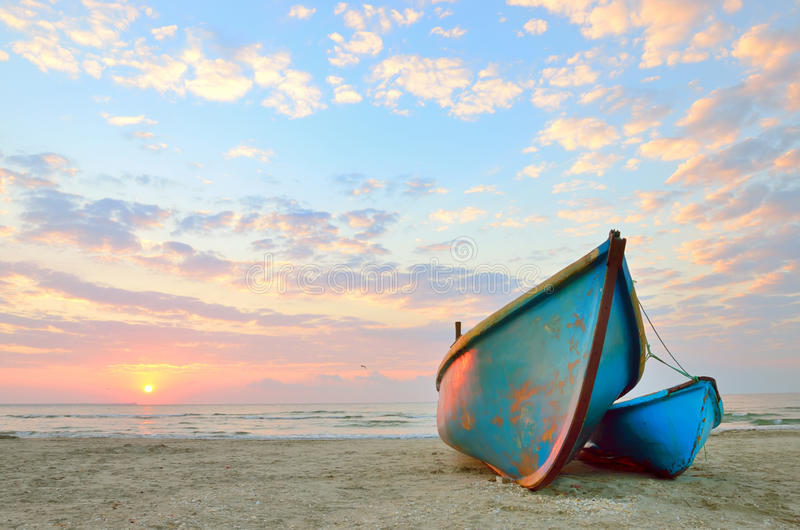 Голубая рыбацкая лодка на восходе солнца стоковое изображение rf