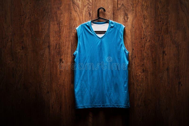 Голубая смертная казнь через повешение jersey баскетбола на деревянной стене стоковая фотография