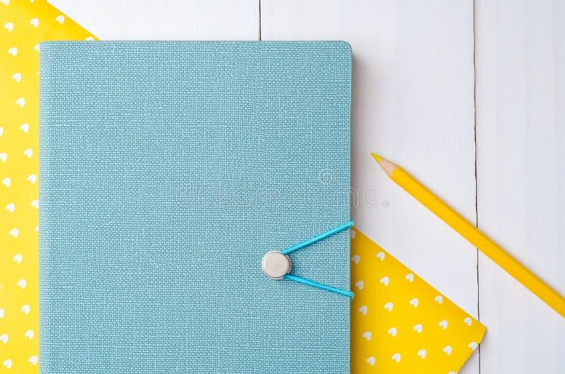 Голубая тетрадь с цветом рисовала на желтой бумаге стоковая фотография