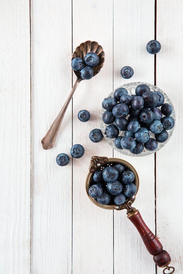 Голубики или черники на белой деревянной таблице стоковое изображение