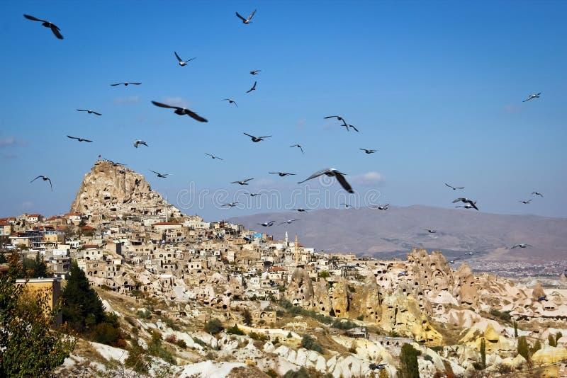 Голуби летания, старый город Cappadocia Турция стоковые фото