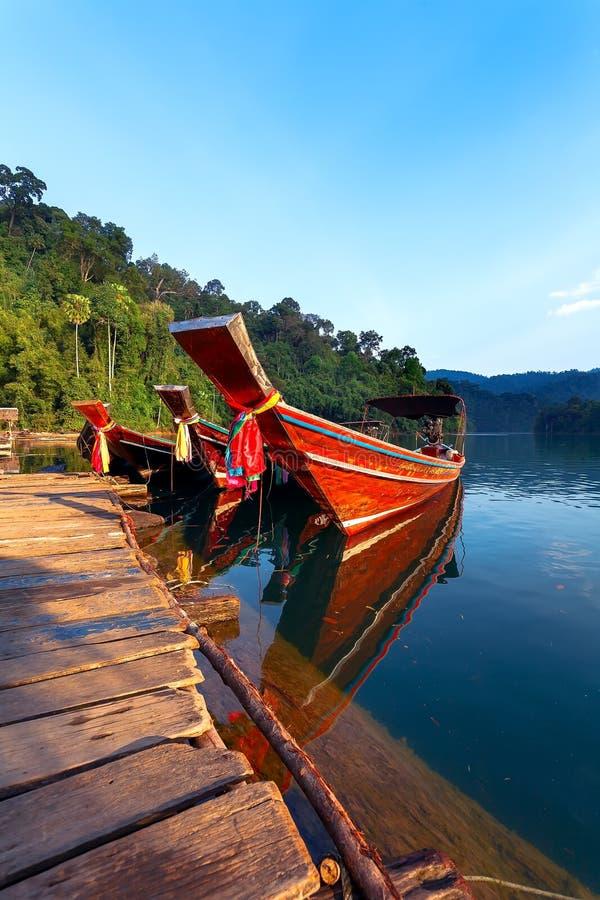 Голубое озеро и 3 деревянных шлюпки стоковое изображение rf