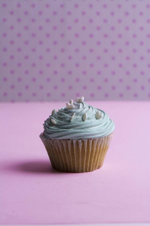 Голубое пирожное с взбитой сливк, и сердце брызгают на розовой точке стоковое фото