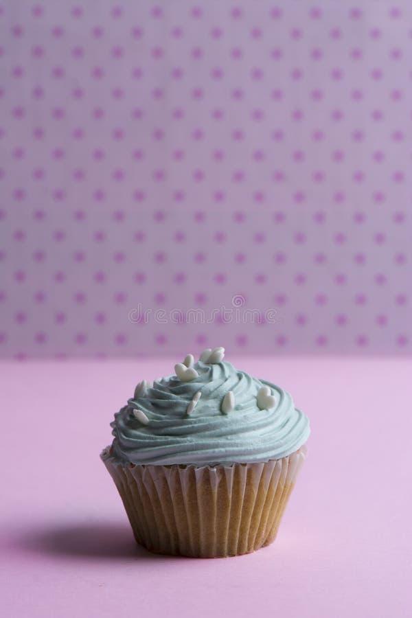 Голубое пирожное с взбитой сливк, и сердце брызгают на розовой точке стоковая фотография